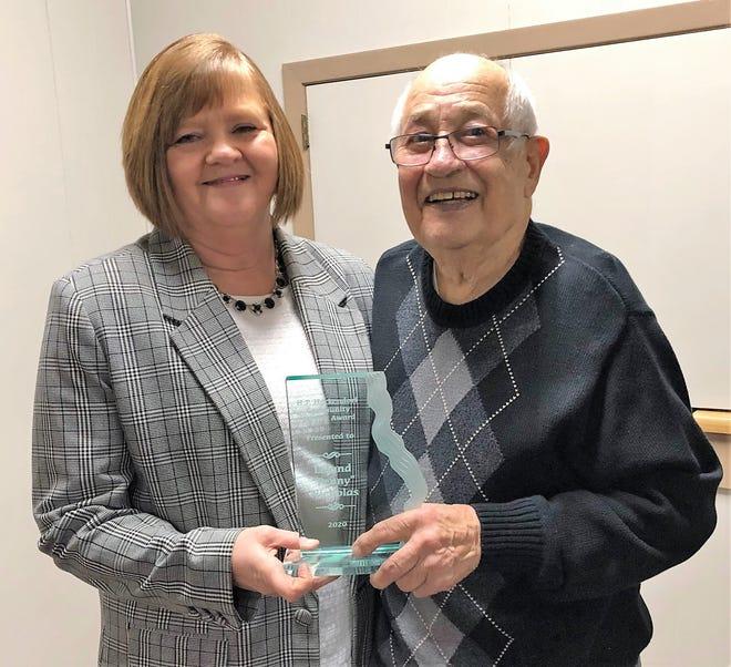 "N.E.W. Credit Union President Lisa Gilligan, left, presents the 2020 Harold P. Heckendorf Community Service Award to Leland ""Penny"" Nicholas of Oconto Falls."