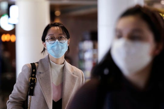 Travelers at Seattle-Tacoma International Airport wear masks Tuesday,  in SeaTac, Wash. Six of the 18 Western Washington residents with the coronavirus have died as health officials rush to test more suspected cases and communities brace for spread of the disease.