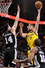 Indiana Pacers' Domantas Sabonis (11) shoots against San Antonio Spurs' Drew Eubanks (14) and DeMar DeRozan during the first half of an NBA basketball game, Monday, March 2, 2020, in San Antonio. (AP Photo/Darren Abate)