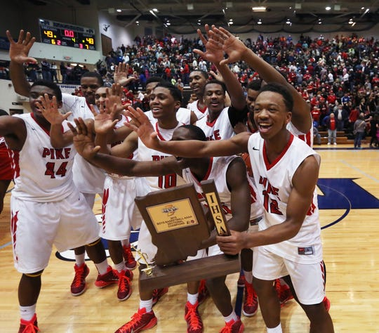 Pike's Justin Thomas (right), the team's high-scorer with 21 points, celebrates with his teammates after the school won its fifth consecutive sectional by beating Class 4A No. 1 Southport 49-48., March 7, 2015.