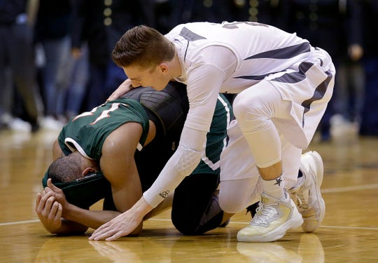 Lawrence Central's Kyle Guy (24) consoles Tech's CJ Walker (11) following  their IHSAA Boys Sectional Tournament game, March 1, 2016, evening at Arsenal Technical High School.