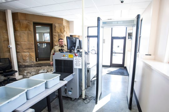 Johnson County Sheriff Deputies Jon Smith stands behind equipment for screening, including an X-ray machine and a metal detector, Tuesday, March 3, 2020, at the Johnson County Courthouse in Iowa City, Iowa.