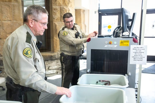 Johnson County Sheriff Deputies Dave Stanton, left, and Jon Smith work at the public entrance screening people, Tuesday, March 3, 2020, at the Johnson County Courthouse in Iowa City, Iowa.