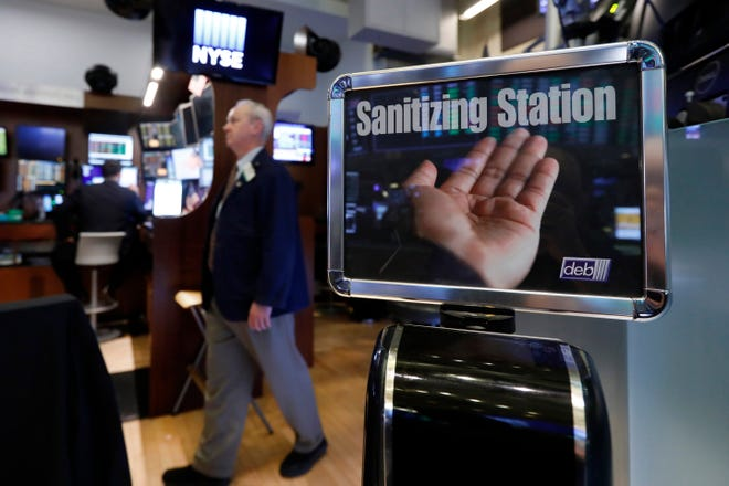 """A trader passes a hand sanitizing station on the floor of the New York Stock Exchange, Tuesday, March 3, 2020. Federal Reserve Chairman Jerome Powell noted that the coronavirus """"poses evolving risks to economic activity."""" (AP Photo/Richard Drew)"""