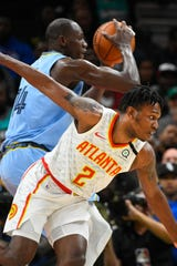 Atlanta Hawks guard Treveon Graham (2) defends against Memphis Grizzlies center Gorgui Dieng during the first half of an NBA basketball game Monday, March 2, 2020, in Atlanta. (AP Photo/John Amis)