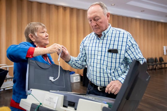 Poll worker Candis Schoenberger hands J.B. Kiser the stylus Tuesday, March 3, 2020, while voting at The Great Hall in Germantown.