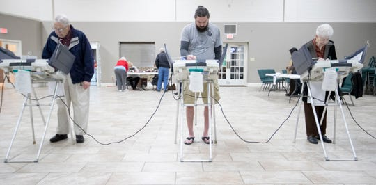 Walter Cline (from left), Franklin Simpson and Lynn Cline cast their ballots Tuesday, March 3, 2020, while voting at Whitten Memorial Baptist Church in Memphis.