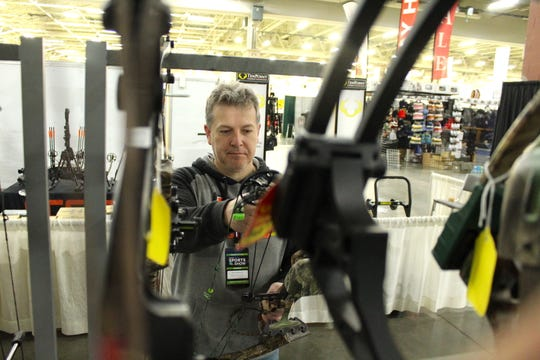 Rob Schaffhauser of West Town Archery puts a compound bow on a rack at the Milwaukee Journal Sentinel Sports Show.