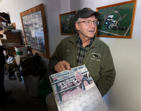 Paul Adams holds a calendar that featured his daughter, Becky, and their dairy herd.