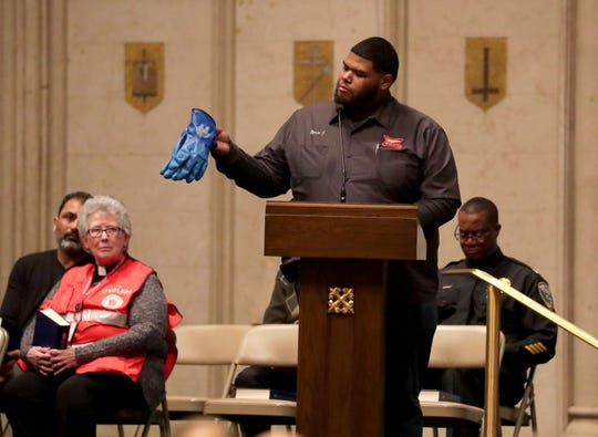 Molson Coors employee Byron Johnson holds up a pair of blue rubber work gloves that he wore on the day of the shooting as he speaks during a vigil at the Church of the Gesu on the Marquette University campus in Milwaukee on Monday. The vigil, held by the Near West Side Partners, is in the wake of a mass shooting at the Molson Coors Brewery last week that left six people dead including the shooter, who took his own life.