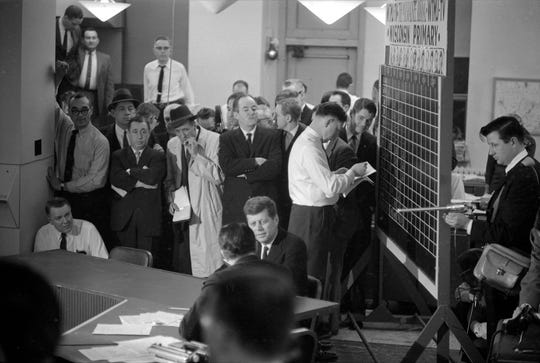 Sen. John F. Kennedy, center, is interviewed by NBC reporter Sander Vanocur in The MIlwaukee Journal newsroom on April 5, 1960, the night of the Wisconsin primary. Kennedy's chief rival, Sen. Hubert Humphrey, is seen standing behind Kennedy with his arms folded. At right, votes are tallied on a chalkboard while a member of the TV crew holds a boom mic to pick up the interview. This photo was published in the April 6, 1960, Milwaukee Journal.