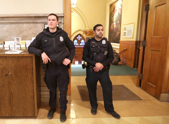Police officers stand inside at the rear of the Church of the Gesu shortly before the vigil.