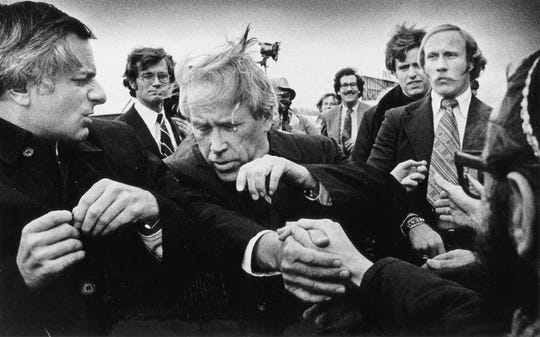 """1976: At Madison's airport, a demonstrator spits in the face of Washington Sen. Henry Jackson during Jackson's campaign stop during the Wisconsin primary on March 30, 1976. Jackson had been known as a """"hawk"""" on the Vietnam War. Madison, the home of the University of Wisconsin, was noted for its anti-war protests."""