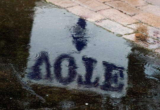 A vote sign is reflected in a flooded sidewalk during the rain on Primary Election Day in Montgomery, Ala., on Tuesday March 3, 2020.