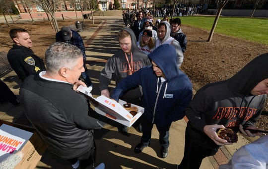 Auburn head coach Bruce Pearl gives donuts and bagels out to students waiting in line before a game against Iowa State on Saturday, Jan. 25, 2020 in Auburn, Ala.