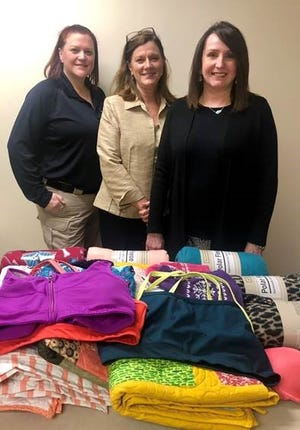 Dani Barker (left), Susan Miller (middle) and Debbie Curtis (right) pose with a donation of undergarments and blankets to the sexual assault center at Saint Thomas Rutherford Hospital.