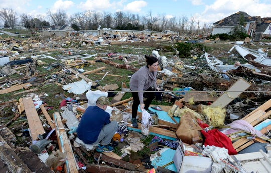 Karen Kopinski and Justin Birdwell looks for her the belongings of her sister-in-law, Tracy Savage, after a tornado destroyed her home in the Echo Valley Estates on on March 3 in Putnam County, Tenn.