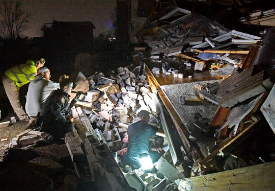 Metro off-duty police officers Tyler Manivong, center, in black, and Nate Larson, center, in camo, dig to free Bill and Shirley Wallace from their Barrett Drive home that collapsed on them, trapping them under rubble after a tornado.  Mt. Juliet, Tenn. Tuesday, March 3, 2020.