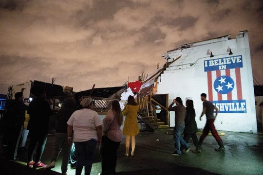 People stand outside the Basement East music venue in East Nashville after it was destroyed by a tornado Tuesday, March 3, 2020.