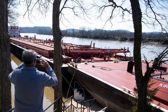 Crews collect barges from the Cumberland River in the Charlotte Park neighborhood Tuesday in Nashville. Several barges crashed together against people's personal docks after a tornado early Tuesday morning.