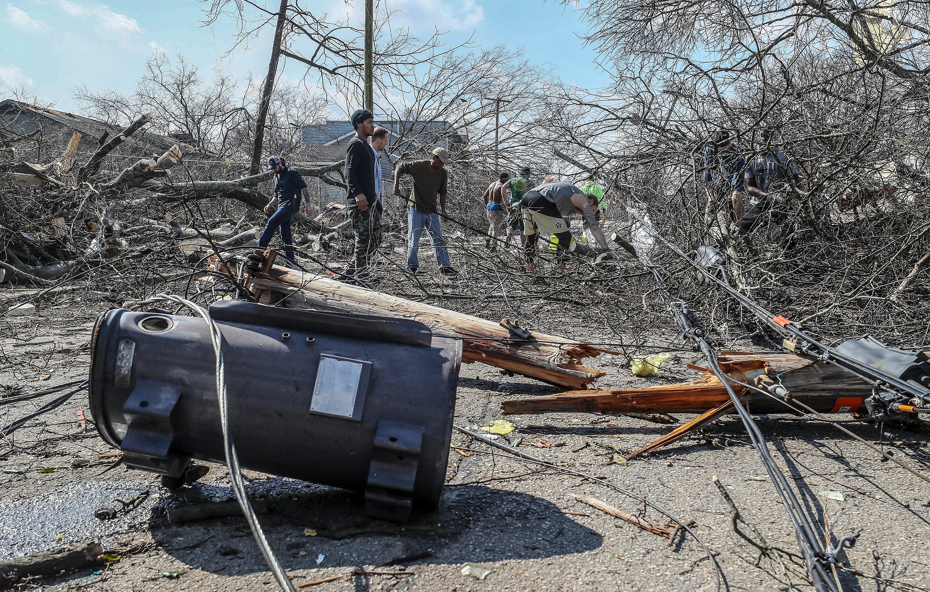 Residents, friends and volunteers work to clear the debris along Cockrill Street in North Nashville on March 3, 2020.
