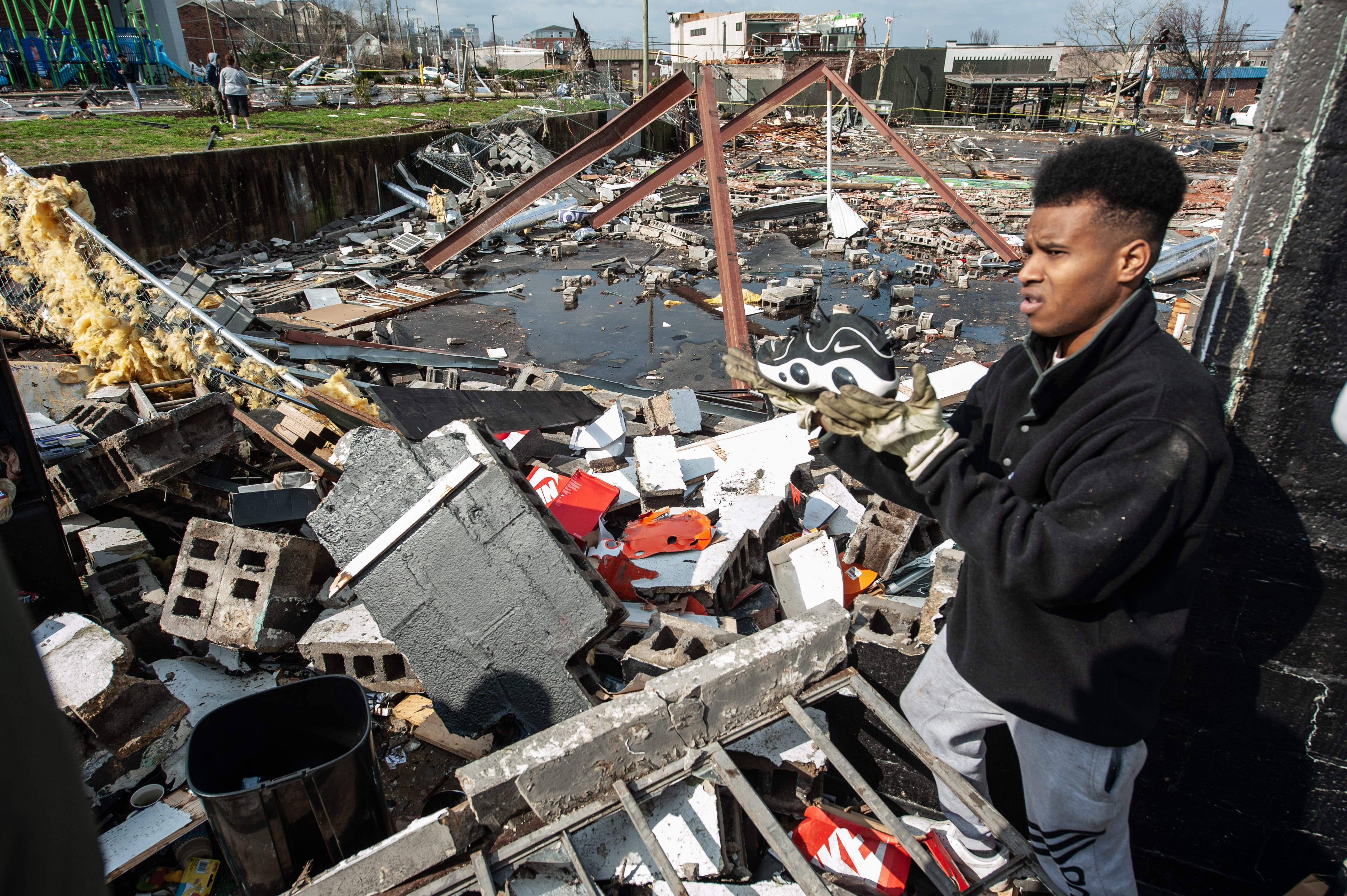Dominique Fowler helps salvage items from Music City Vintage in East Nashville on Tuesday after a tornado ripped through the area, obliterating buildings and killing at least 25 people across the state.