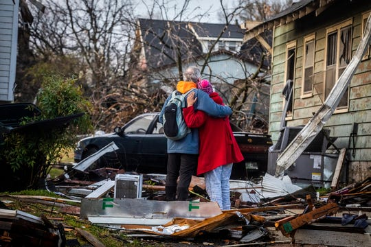 Lee Tucker, left, and Sharlyn Spicer, longtime next-door neighbors on Holly Street, embrace as they survey the damage done to their homes after a tornado struck East Nashville on Tuesday, March 3, 2020.