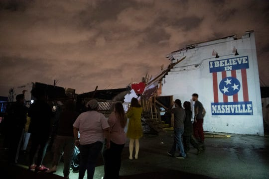 People stand outside the Basement East music venue in East Nashville after it was destroyed by a tornado on Tuesday, March 3, 2020.