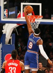 New York Knicks guard RJ Barrett (9) goes up for a dunk shot as Houston Rockets forward Robert Covington (33) looks on during the first half at Madison Square Garden.
