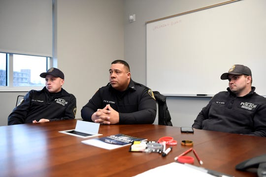 (from left) Garfield officers Sebastian Tyburski, Kevin Otero, and Randy Kata talk about a call they responded to during a snowstorm where CPR and a defibrillator were needed to resuscitate a man. Photographed at the Garfield Police Department on Tuesday, March 3, 2020.