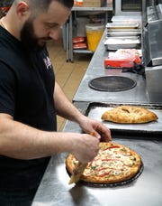 Luigi Mainella brushes some butter onto a pizza crust at Luigi's in Livonia.