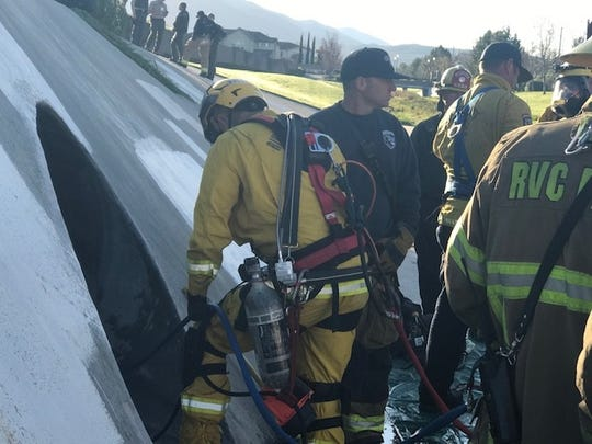 Emergency personnel prepare to rescue a man trapped Tuesday inside a Temecula storm drain.