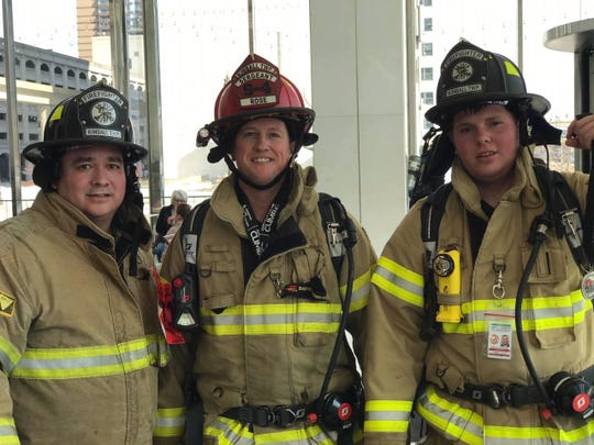 (from left): Firefighter Eduardo, Sgt. Chris Rose and firefighter Jacob Eschenburg climbed up and down 55 floors in full fire gear and breathing apparatus, which weighed approximately 80 pounds.