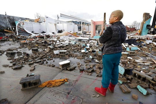 Faith Patton looks over buildings destroyed by storms Tuesday, March 3, 2020, in Nashville, Tenn. Tornadoes ripped across Tennessee early Tuesday, shredding buildings and killing multiple people. Patton lives near the damaged area but her home was intact. (AP Photo/Mark Humphrey)