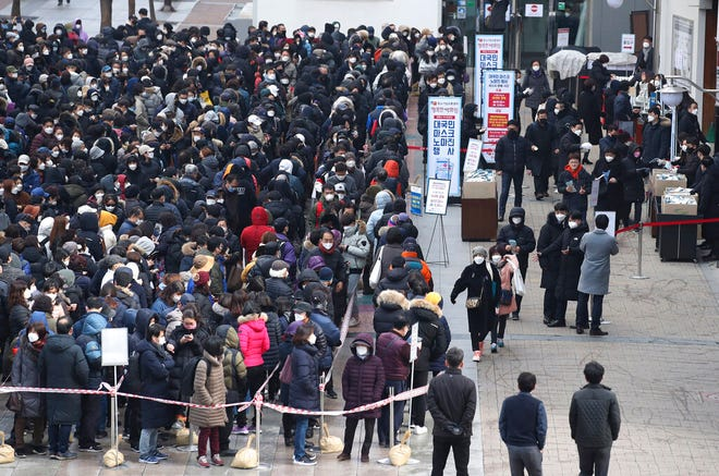 Hundreds of people line up to buy face masks to protect themselves from the coronavirus in front of a department store in Seoul, South Korea, Tuesday, March 3, 2020. China's coronavirus caseload continued to wane Tuesday even as the epidemic took a firmer hold beyond Asia, with three countries now exceeding 1,000 cases and the U.S. reporting its sixth death. (Hong Hae-in/Yonhap via AP)