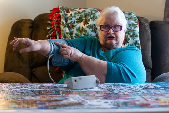 Sandy Eaton, 66, demonstrates how she checks her own blood pressure from her home in Tully, Onondaga County. She's one of 145 patients across central New York using biometric monitoring devices, like blood pressure cuffs and scales, distributed by Syracuse-based Nascentia Health.