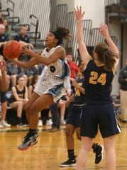 Kearney's Marianna Freeman, left, drives to the basket past Victor's Kaitlin Murphy, right, and Ijeoma Nwugwo.
