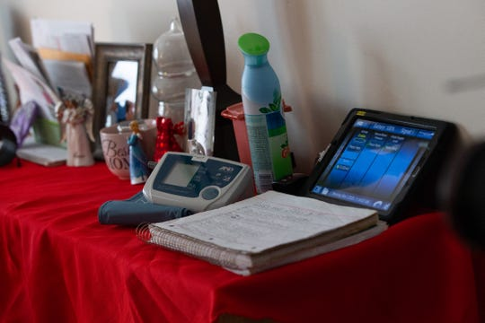 Sandy Eaton, 66, keeps a log of her blood pressure, heart rate and blood oxygen level at a table in her living room at her home in Tully, Onondaga County. She's one of 145 patients across central New York using biometric monitoring devices, like blood pressure cuffs and scales, distributed by Syracuse-based Nascentia Health.