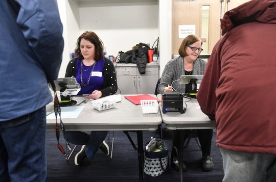 Election workers check voter's information during Minnesota presidential primary voting Tuesday, March 3, 2020, at St. Cloud State University.