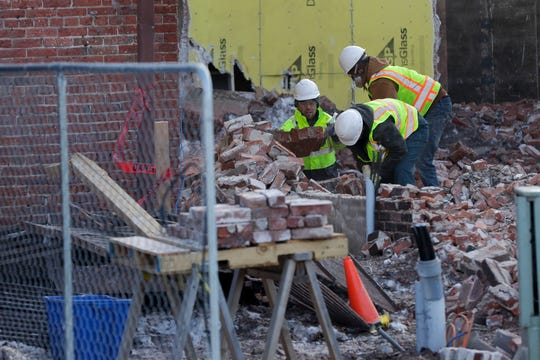 Workers clear rubble from the demolition site of the Fox Theater on Tuesday in downtown Stevens Point.