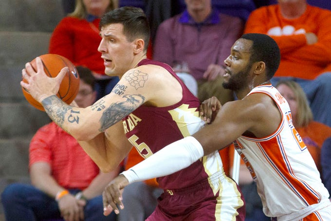 Feb 29, 2020; Clemson, South Carolina, USA; Florida State Seminoles center Dominik Olejniczak (15) is defended by Clemson Tigers forward Aamir Simms (25) during the first half at Littlejohn Coliseum. Mandatory Credit: Joshua S. Kelly-USA TODAY Sports