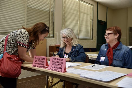 Maru Schweizer (left), 43, signs in to her polling place at Grace Lutheran Church in Ventura on Tuesday with the help of Kathy Kircher and Lisa Fox.