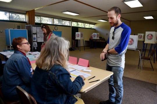Alex Taroyan, 23, signs in at his polling place at Grace Lutheran Church in Ventura on Tuesday with the help of poll workers Kathy Kircher and Lisa Fox.