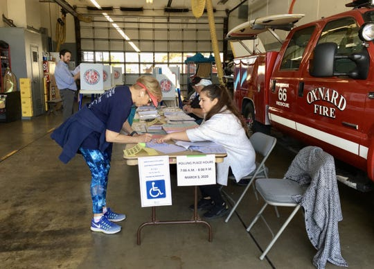 Kendall Mattina, 70, signs in to vote with help from Brenda Sanchez at Fire Station 6 in Oxnard on Tuesday.