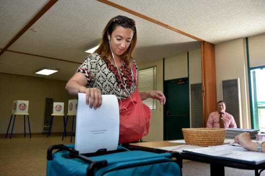 Maru Schweizer, 43, submits her ballot at Grace Lutheran Church in Ventura on Tuesday.