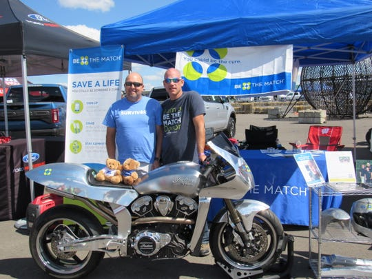Todd Euen of Johnstown, Pennsylvania, and Mark Ecklund of Weston stand behind the Be the Match motorcycle that Ecklund designed and built. Ecklund donated life-saving stem cells to Euen.