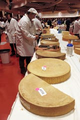 Judge Christophe Megevand inspects a wheel of Gruyere cheese at the biennial World Championship Cheese Contest, Tuesday, March 3, 2020, at the Monona Terrace Convention Center in Madison, Wis. It's the largest technical cheese, butter and yogurt competition in the world. This year the competition had a record 3,667 entries from 26 nations. (AP Photo/Carrie Antlfinger)