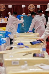 World Championship Cheese Contest committee members Gary Grossen, left, Gordy Bergemann, right, and Dan Stearns, rear, turn a block of Swiss cheese at the biennial World Championship Cheese Contest, Tuesday, March 3, 2020, at the Monona Terrace Convention Center in Madison, Wis. It's the largest technical cheese, butter and yogurt competition in the world. This year the competition had a record 3,667 entries from 26 nations. (AP Photo/Carrie Antlfinger)