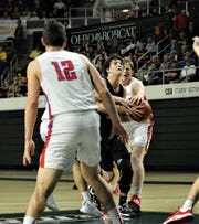 Crooksville's Caden Miller drives into the several Peebles defenders in Monday's Division IV district semifinal at Ohio University's Convo Center. The Ceramics lost 63-43.