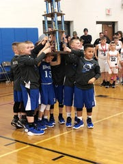 The Zanesville fourth grade team holds up the trophy for winning the state championship for their division at the 2020 Ohio Youth Basketball Division II State Championship in Columbus.